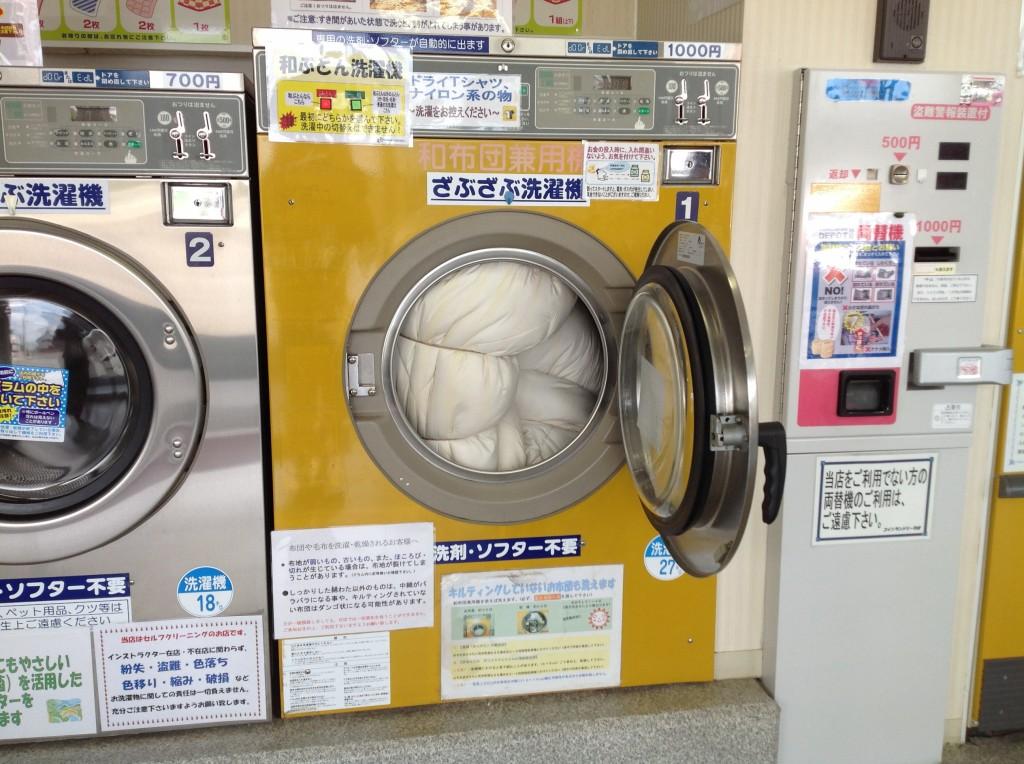 麻紐で縛った敷布団を洗濯機に入れる