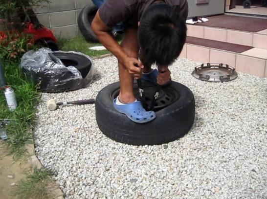 タイヤレバーの曲がっている部分を使ってホイールとタイヤを剥がす
