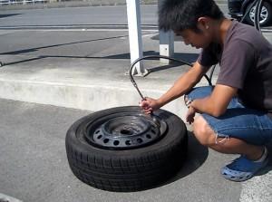 タンクつきのエアーコンプレッサーで組み換えたタイヤに空気を入れる