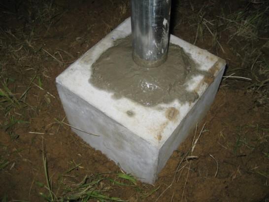 フェンス基礎石と単管パイプの隙間に生コンを打つ
