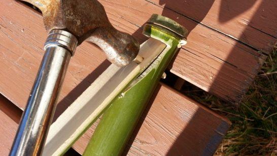 金槌で竹の棒を挿入する