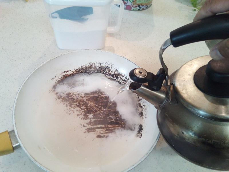 過炭酸ナトリウムが入った焦げ付いたフライパンにお湯を注ぐ