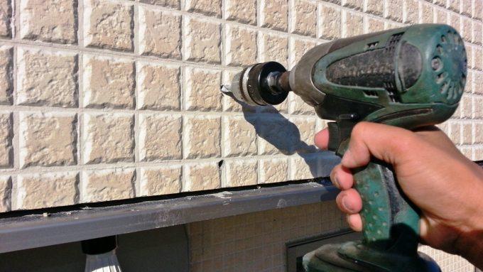 オーニングを取り付けるためにインパクトドライバーで壁に穴をあける