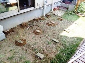 ウッドデッキの基礎となるレンガを地面に並べる